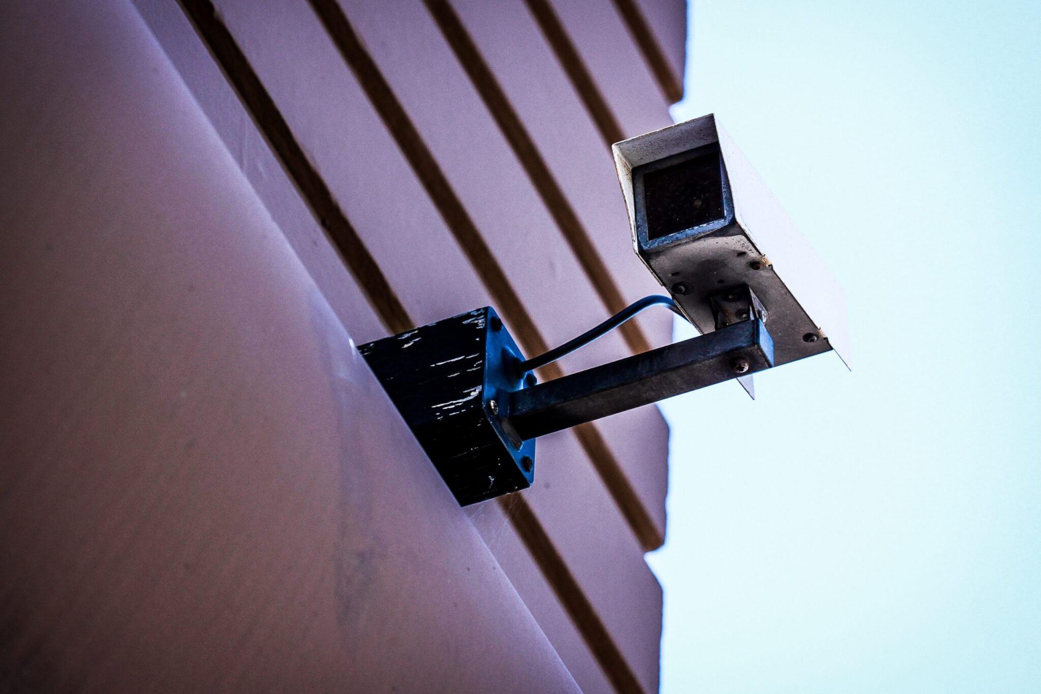 gray surveillance camera on gray wall